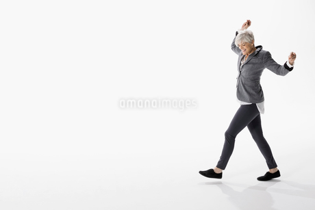 Energetic senior woman dancing against white backgroundの写真素材 [FYI02315979]
