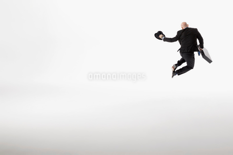 Playful businessman with briefcase jumping, clicking heels against white backgroundの写真素材 [FYI02316022]