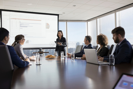 Businesswoman with digital tablet leading presentation at projection screen in conference room meetiの写真素材 [FYI02316062]