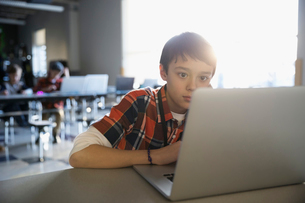 Focused pre-adolescent boy using laptop in classroomの写真素材 [FYI02316066]