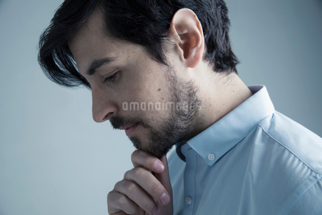 Profile portrait serious, pensive brunette Caucasian man with beard looking down with hand on chinの写真素材 [FYI02316099]