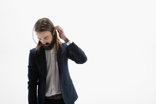 Cool businessman with beard looking down against white backgroundの写真素材 [FYI02316251]