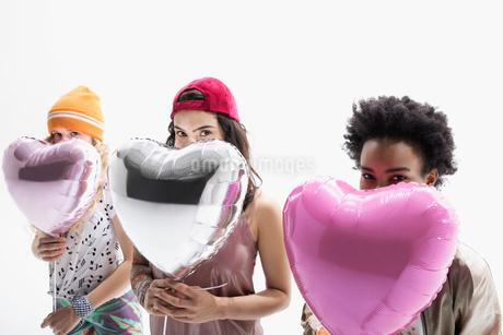 Portrait smiling women friends hiding behind heart-shape balloons against white backgroundの写真素材 [FYI02316257]