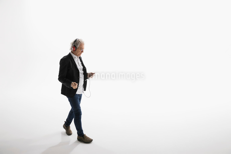 Businessman listening to music with headphones and mp3 player against white backgroundの写真素材 [FYI02316281]