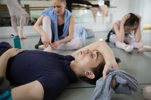 Tired male ballet dancer resting on floor in dance studioの写真素材 [FYI02316310]