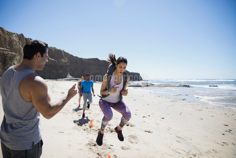 Young woman doing crossfit exercises between cones on sunny beachの写真素材 [FYI02316356]