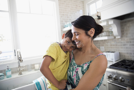 Portrait smiling mother holding son in kitchenの写真素材 [FYI02316407]
