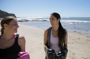 Women wearing boxing gloves on sunny beachの写真素材 [FYI02316409]