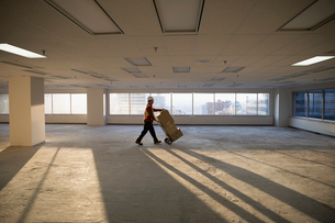 Construction worker moving cardboard boxes on handcart in sunny empty, unfinished highrise officeの写真素材 [FYI02316434]