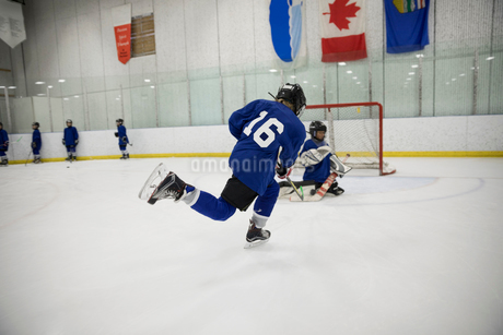 Boy ice hockey player taking a shot at goal on ice hockey rinkの写真素材 [FYI02316570]