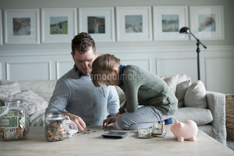 Father teaching daughter counting allowance money in living roomの写真素材 [FYI02316657]