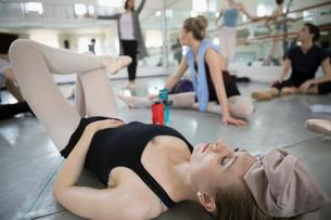 Tired female ballet dancer resting on floor in dance studioの写真素材 [FYI02316707]
