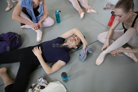 Tired male ballet dancer resting on floor in dance studioの写真素材 [FYI02316710]