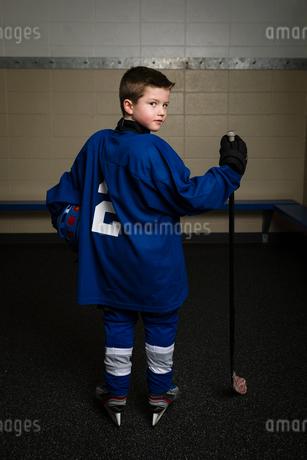 Portrait serious boy ice hockey player in uniform holding hockey stick and helmetの写真素材 [FYI02316737]