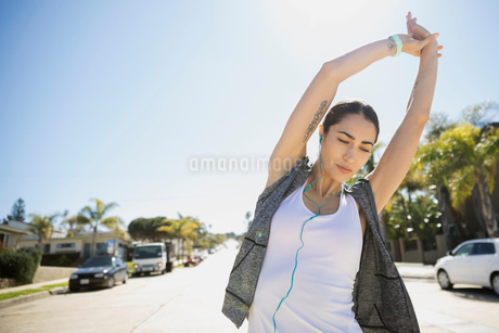 Female Latina runner stretching arms on sunny roadの写真素材 [FYI02316803]