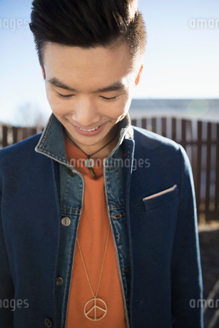 Close up smiling young stylish Chinese man looking downの写真素材 [FYI02316816]