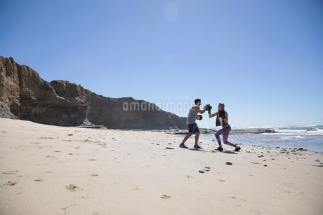 Man and woman boxing on sunny beachの写真素材 [FYI02316835]