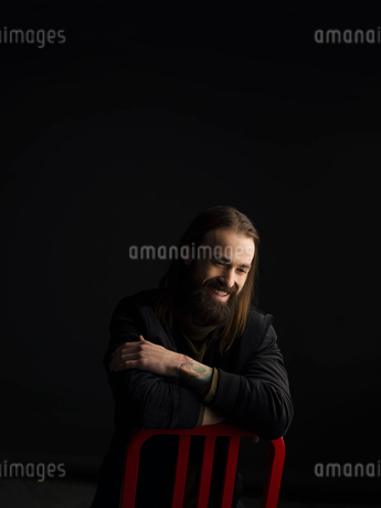 Portrait smiling brunette man with beard leaning on chair and looking down against black backgroundの写真素材 [FYI02316846]