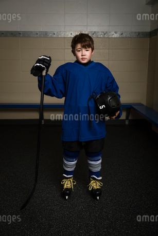 Portrait serious boy ice hockey player in uniform holding hockey stick and helmetの写真素材 [FYI02316883]