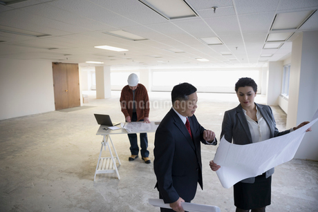 Architects reviewing blueprints in unfinished, empty open plan officeの写真素材 [FYI02316893]