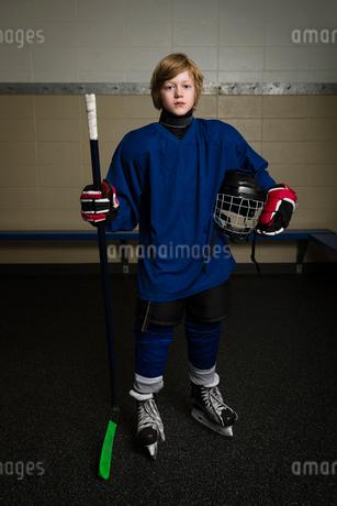 Portrait serious boy ice hockey player in uniform holding hockey stick and helmetの写真素材 [FYI02316917]
