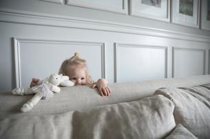 Girl with stuffed animal hiding behind living room sofaの写真素材 [FYI02316921]