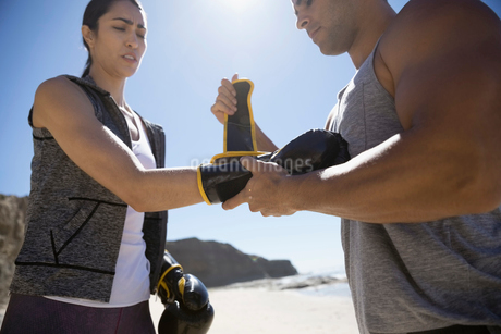 Man helping woman putting on boxing gloves on sunny beachの写真素材 [FYI02316923]