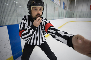 Male ice hockey referee blowing whistle on ice hockey rinkの写真素材 [FYI02316947]