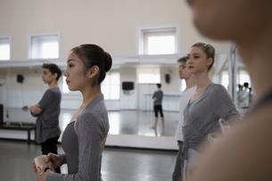 Attentive ballet dancers listening in dance studioの写真素材 [FYI02316960]