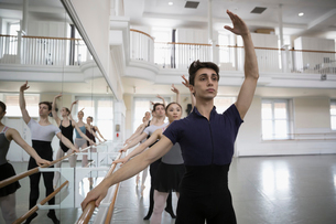 Focused ballet dancers practicing fourth position at barre in dance studioの写真素材 [FYI02316991]
