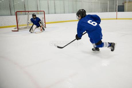 Boy ice hockey player taking a shot at goal on ice hockey rinkの写真素材 [FYI02317007]