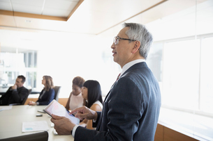 Senior businessman with digital tablet leading conference room meetingの写真素材 [FYI02317071]