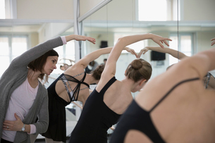 Female instructor guiding ballet dancers practicing at barre in dance studioの写真素材 [FYI02317083]