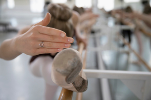Female ballet dancer with heart-shape ring practicing at barre in dance studioの写真素材 [FYI02317156]