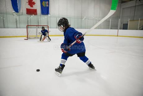 Boy ice hockey player taking a shot at goal on ice hockey rinkの写真素材 [FYI02317180]