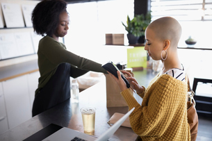 Young woman with shaved head using credit card reader at juice barの写真素材 [FYI02317191]