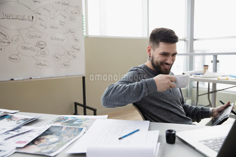 Smiling creative male designer drinking coffee and using graphics tablet in officeの写真素材 [FYI02317221]