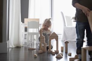 Girl playing with wood building blocks on floorの写真素材 [FYI02317226]
