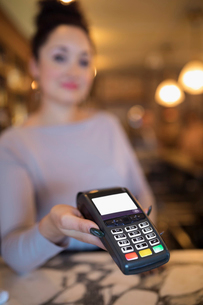 Close up female bartender using credit card readerの写真素材 [FYI02317261]