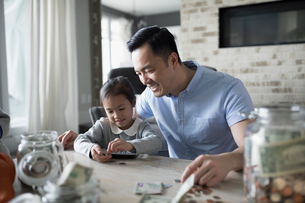 Father teaching daughter counting allowance moneyの写真素材 [FYI02317269]