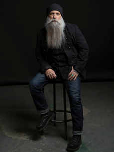 Portrait confident hipster man with long gray beard on stool against black backgroundの写真素材 [FYI02317399]