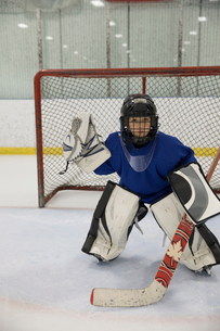 Portrait focused boy ice hockey goalie player at net on iceの写真素材 [FYI02317464]