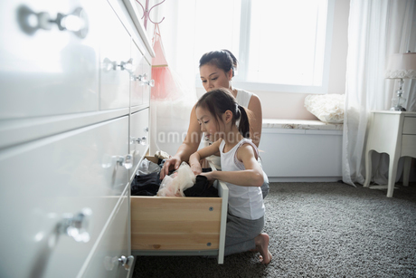 Mother and daughter putting laundry away in dresser drawer in bedroomの写真素材 [FYI02317592]