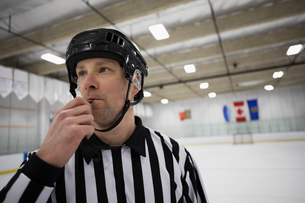 Male ice hockey referee blowing whistle on ice hockey rinkの写真素材 [FYI02317646]