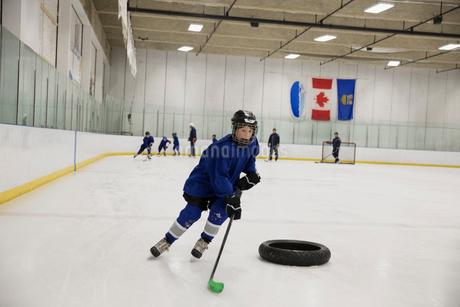 Boy ice hockey player practicing drills on ice hockey rinkの写真素材 [FYI02317701]