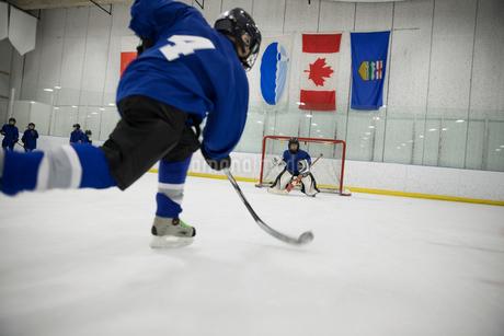 Boy ice hockey player taking a shot at goal on ice hockey rinkの写真素材 [FYI02317713]