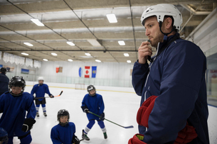 Male ice hockey coach blowing whistle at players on ice hockey rinkの写真素材 [FYI02317718]