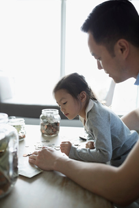 Father teaching daughter counting allowance moneyの写真素材 [FYI02317729]