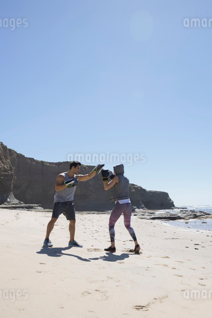 Man and woman boxing on sunny beachの写真素材 [FYI02317763]