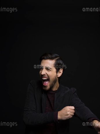 Portrait exuberant brunette man with beard laughing and looking away against black backgroundの写真素材 [FYI02317848]